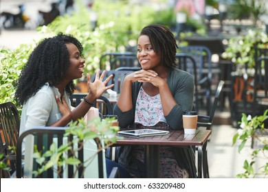 Pretty African-American woman telling story to her female friend