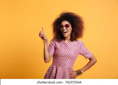 Pretty afro american retro woman with afro hairstyle pointing with finger up, looking at camera, isolated on yellow background