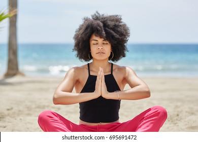 Pretty afro american woman meditating on beach