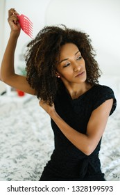 Pretty afro hairstyle woman using comb for untangle her curly hair. Black female beauty and style tips concept.