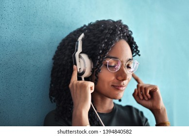 Pretty Afro woman listening to music on headphones.