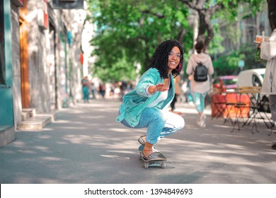 Pretty Afro woman skateboarding on the street.