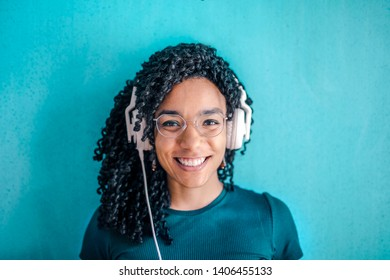 Pretty Afro woman smiling and listening to music on headset.