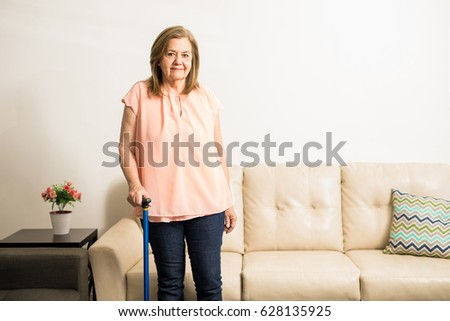 Pretty aged granny using a blue cane to stand up comfortably and walk at home