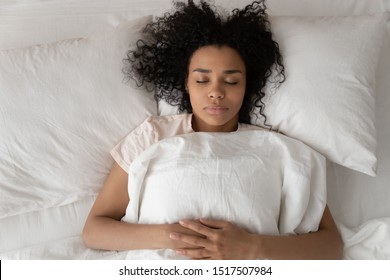Pretty alone african 30s woman lying down in bed on memory foam pillow sleeping in comfortable mattress close up top view, millennial female closed eyes see sweet dreams care of body mind rest concept