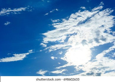 pretty amazing blue sky and clouds with sun for background. sun light shining over the sky behind the clouds.