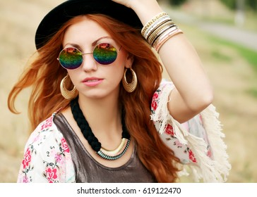 Pretty amazing free red-haired hippie girl. Closeup face portrait of beautiful young woman wearing boho chic clothes, hat and mirror sunglasses. Artsy bohemian style.