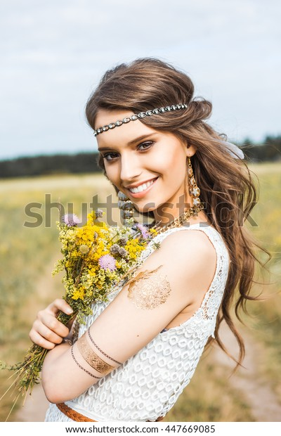 Pretty amazing gentle young hippie girl on the nature in the open air, the feathers in her hair, white dress, leather and gold accessories, flash tattoo, indie, Bohemia, bo-ho style, fashion, flowers