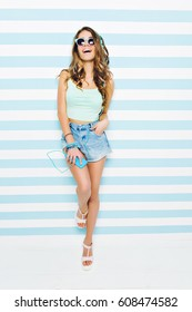 Pretty amazing young woman with long brunette curly hair, in jeans shorts on heels, in blue sunglasses laughing on striped white blue background. Listening to music through headphones, summer time