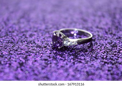 A pretty amethyst ring on a purple sparkling surface