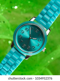 Pretty aqua designer watch against an abstract bright green sparkly background