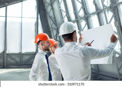 Pretty architect is explaining to builders the plan of construction. He is holding a pen and pointing it at the blueprint with seriousness. The foreman is smiling. Copy space in left side