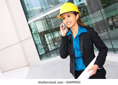 A pretty asian architect woman at building site on phone