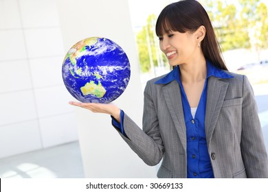 A pretty asian business woman at office holding globe of earth