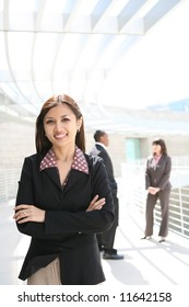 A pretty asian business woman on at company with co-workers in background