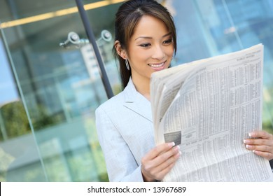 A pretty asian business woman reading the newspaper at office building