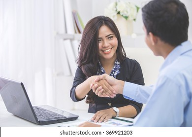 Pretty asian business woman shaking hands with businessman in her office during meeting