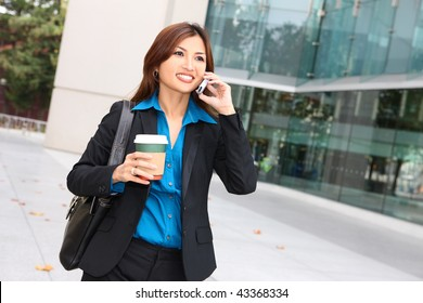 A pretty asian business woman walking with coffee talking on phone