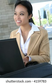 A pretty asian business woman working on her laptop computer