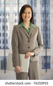 Pretty Asian businesswoman holding a laptop computer