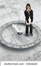 Pretty Asian businesswoman with laptop computer standing on a map with a compass background