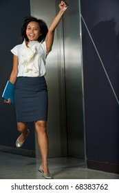 Pretty Asian businesswoman in white blouse, skirt, jumping with raised arm pumping fist celebrating victory in an office environment. 20s female Thai model of Chinese descent looking at camera