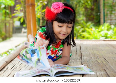 Pretty Asian Child reading book in wood cottage