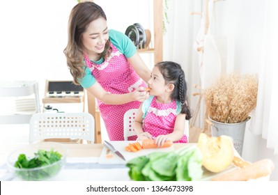 pretty asian children bite organic carrot, attractive asian female holding and feeding fruit to her daughter, family activity, children nutrition