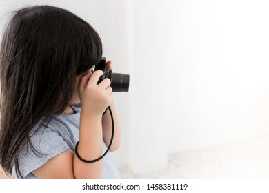 pretty Asian children holding digital camera and take a photo, she learning to use camera, child development