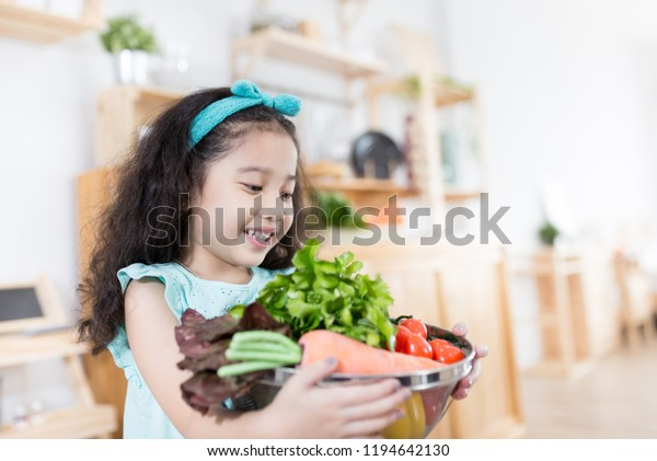 pretty asian children holding vegetables basket, she smiling and feeling happy, cook learning activity