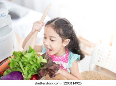 pretty asian children looking vegetables basket, she smiling and feeling happy, she want to eat vegetables, cook learning activity, child nutrition and development
