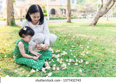pretty asian children and old asian woman sitting on green grass and keep bloom flower, the feeling happy and smile on nature background, elderly happiness activity, mother's day