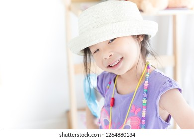 pretty asian children wear a fashion hat before go to travel, kid costume,  family happy day