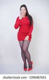 pretty asian chubby woman posing in red knitted dress and black fashionable pantyhose on white studio background
