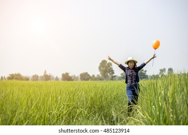 Pretty Asian girl with balloons in green rice hot sun .