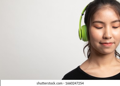 Pretty asian girl listening music with her headphones on white background