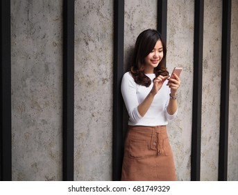 Pretty Asian Girl looking at SmartPhone