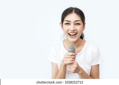 Pretty asian girl with the microphone in her hand isolated on white background, Closeup portrait of asian woman singing a song. Music and education concept