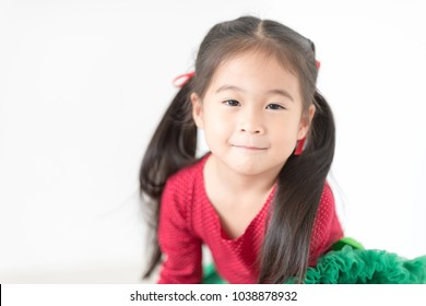 Pretty Asian girl in red and green color on white background. Happy thanksgiving and Christmas Eve Party Concept. She is looking at camera.