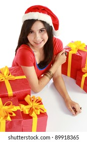 pretty asian girl in santa hat with her xmas gifts isolated on white background