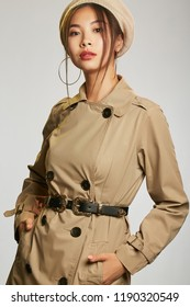 c33b318eb8f943 Pretty Asian lady wearing a beige trench coat, fastened with a black leather  belt.