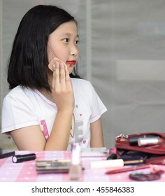 Pretty asian little girl makeup herself