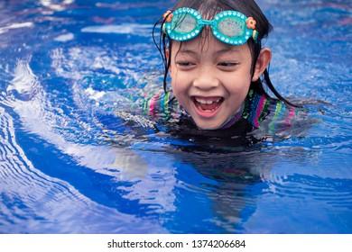 Pretty asian little girl in swimming pool
