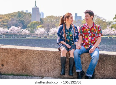Pretty Asian lovers looking at each other in cherry blossom season. The couple hand in hand at Osaka Japanese Castle Area in Osaka, Japan, Asia.
