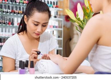Pretty Asian manicurist applying nail polish