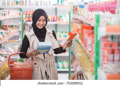 pretty asian muslim woman comparing between two products in supermarket