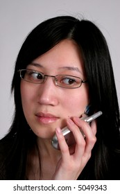 Pretty asian talking on cell phone, looking low and right