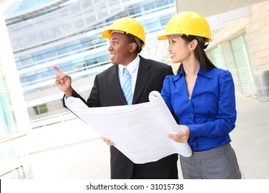 A pretty asian woman and african man working as architects on a construction site