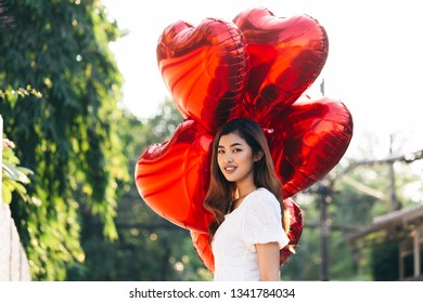 Pretty Asian woman with bunch of red heart shaped balloons looking away while standing on blurred background of park on sunny day