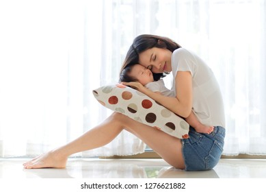 Pretty Asian woman closing her eyes and holding her sleeping baby in her arms sitting together near the window at home. She put her head on baby. Love and touch from mother. Happy family concept.